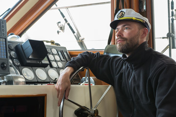 Captain at the helm of boat going along the Pacific Ocean
