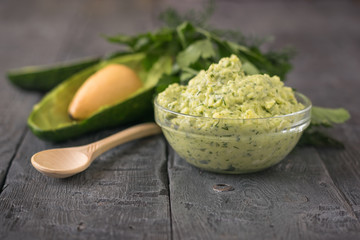 Cream puree avocado with parsley, dill and garlic in a bowl on a rustic table. The dish is vegetarian diet.