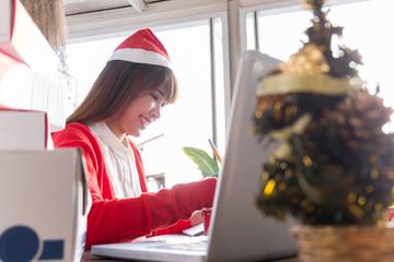 woman wearing santa hat checking order online business
