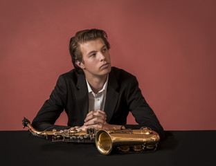 Young man sitting behind saxophone, red background
