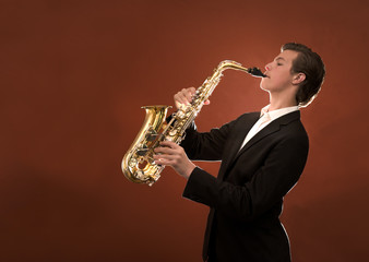 Young man playing saxophone against orange background