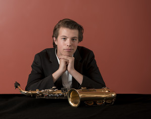 Young man looking at camera, sitting behind saxophone, red background