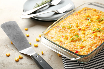 Baking dish with corn pudding on table