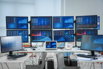 Monitors with stock data on table in office