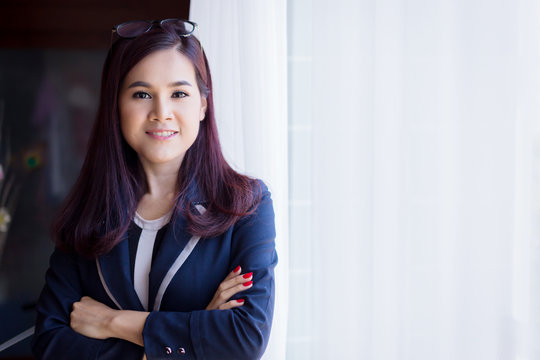 smart beautiful asian businesswoman in suit pose action near white curtain with sunlight from window