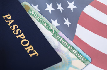 United States of America permanent resident card, green card, displayed with a US flag in the background and a passport in the foreground. Immigration concept.