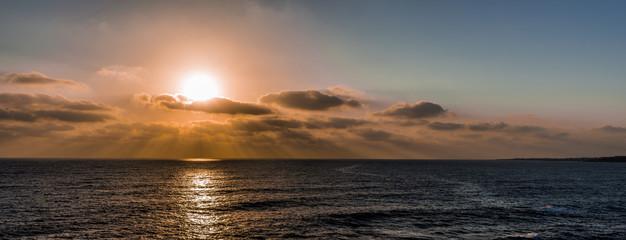The sun sets in dark clouds