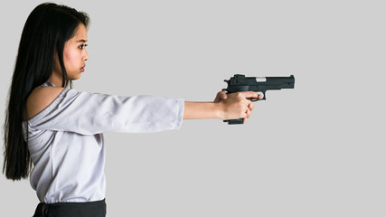An Asian woman is aiming handgun to a target in front of her