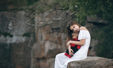 Young model-looking woman sitting on the rocks with a doll on her lap. A teenage girl imagines that she is a mother.