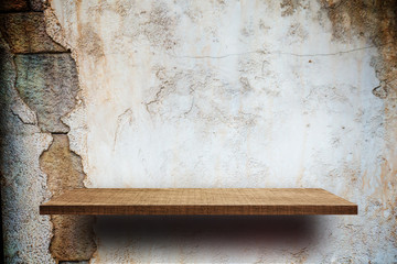Empty wooden shelves display on cracked brick wall
