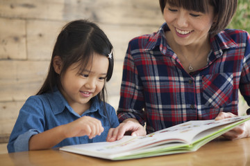 A young mother and a girl read a picture book together.