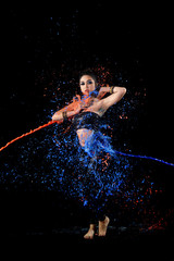 Young asian belly dancer with colorful paint dancing with passion