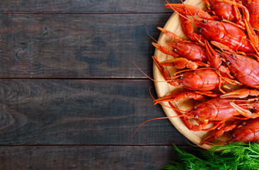 A  pile of tasty boiled crawfish on a round wooden tray on a dark table. Top view. Free space for an inscription.