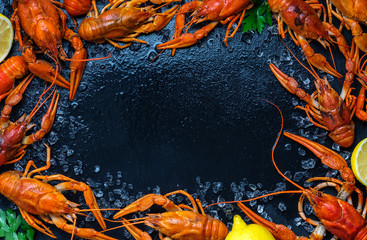 Fresh boiled crawfish with lemons and greens on a dark table with ice