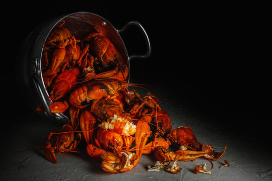 Many crawfish in an aluminum pan on a dark background.