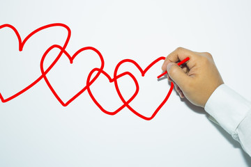 Man's hand with pencil draws hearts