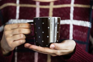 Closeup of woman holding hot drink cup
