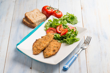 breaded fish fillet with salad