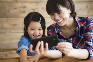 Beautiful young mom and her little daughter are using a smartphone and smiling while sitting on table at home.