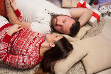 the guy with the girl lying on the floor at the new year Christmas tree