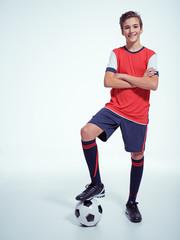 Photo of teen boy in sportswear holding soccer ball