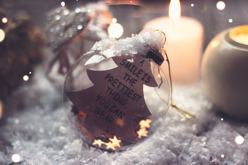 "Christmas and new year background - glass ball with quote ""a smile is the prettiest thing you can wear"", candle and christmas lights on wooden table"