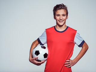 smiling teen boy in sportswear holding soccer ball