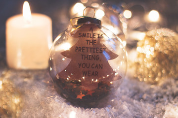 "Christmas and new year background - glass ornament with quote ""a smile is the prettiest thing you can wear"", candle and christmas lights on wooden table"
