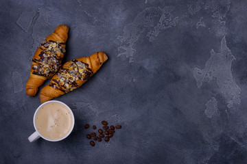 Cappuccino and two croissant on stone table