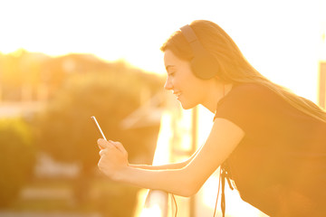 Girl using a smart phone in a balcony at sunset