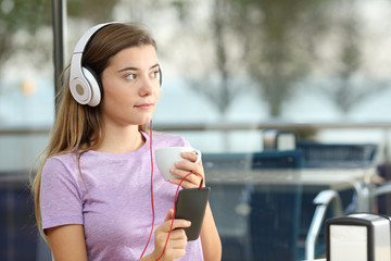 Serious teenager listening to music in a bar