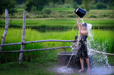 Rural girl is taking a shower from a traditional Groundwater at countryside.