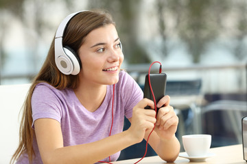 Happy teen listening to music in a coffee shop