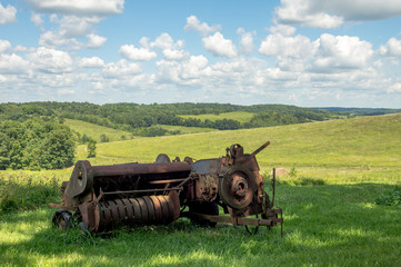 Wall Mural - Rusty Baler with Rolling Hills in the Background