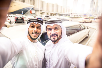 Two arabian businessmen taking selfie near the limousine