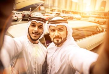 Two arabian businessmen taking selfie near the limousine