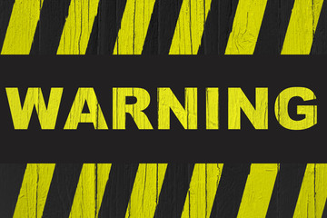 Warning sign with yellow and black stripes painted over cracked wood. Concept image meaning: do not enter the area, caution, danger