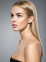 Profile portrait of young woman with long light straight  hair.