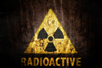 Yellow radioactive (ionizing radiation) danger symbol with word radioactive painted below the sign on a massive concrete wall with dark rustic grunge brown texture background.