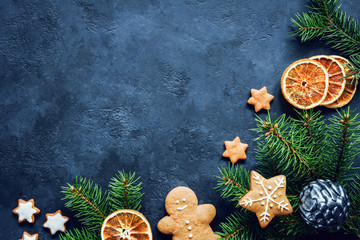Winter holidays Christmas or New Year background with gingerbread cookies, fir tree and dried orange rings. Copy space for your text. Design mock up