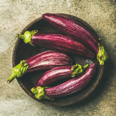 Flat-lay of fresh raw Fall harvest purple eggplants or aubergines in wooden bowl over concrete stone background, top view, square crop. Healthy Autumn vegan cooking ingredient