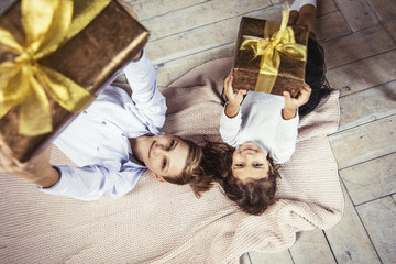 Happy beautiful children boy and girl with gifts in the hands are on the floor together at home