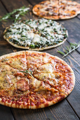 Varied pizzas on a wooden table