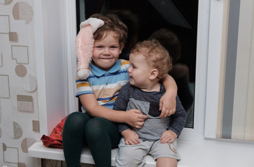 two lovely boy of European appearance sitting on the windowsill