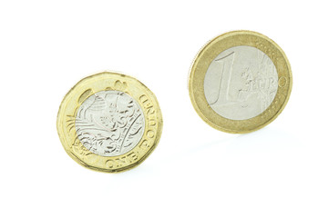 One euro coin and a pound of coin isolated on white