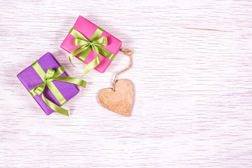 Wooden heart and gift boxes on a white background. Copy space. Bright gift boxes with ribbons.