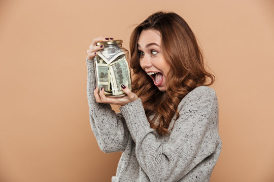 Overjoyed curly brunette girl holding glass jar with her savings