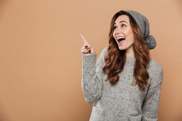 Young happy woman on winter warm hat pointing