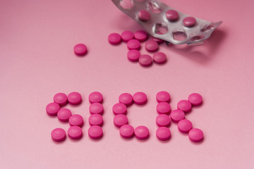 "Pink pills on a pink background. The word ""sick"" of tablets and empty blister. Flat lay"