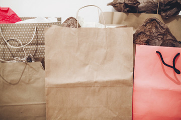 many brown paper bags with presents on background of white wall. black friday, seasonal sale. shopping, christmas shopping concept, space for text. big sale.